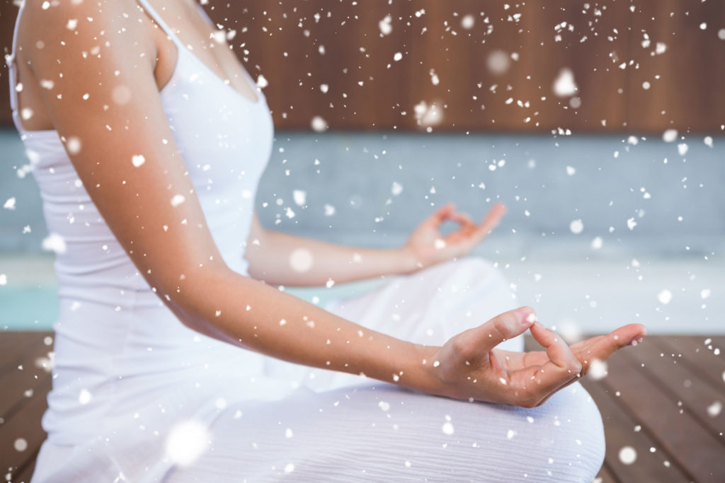31865667 - peaceful woman in white sitting in lotus pose against snow falling